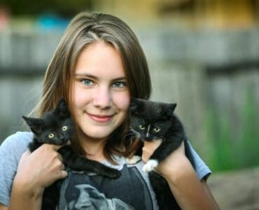 young girl holding two black kittens