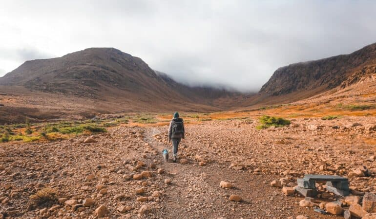 girl hiking with a cat on leash in the Tablelands in Canada
