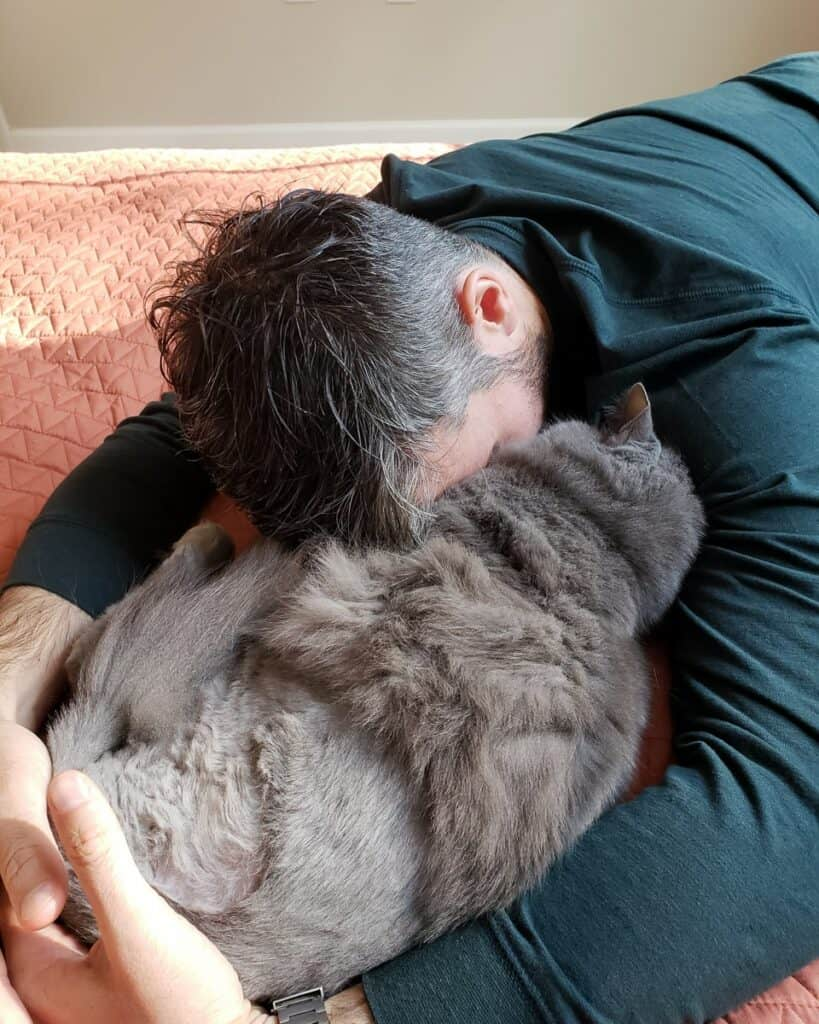man cuddling grey cat who has only three legs from cancer